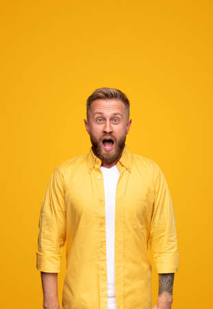 Shocked blond man looking at camera