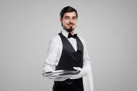 Friendly waiter with tray looking at camera