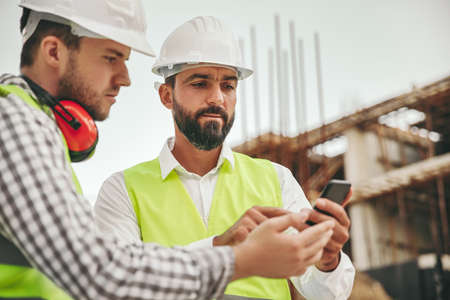 Architects working with smartphone on construction site Archivio Fotografico