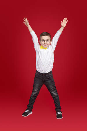 Excited schoolboy with raised hands