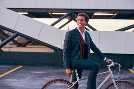 Modern cheerful man with bicycle in business center