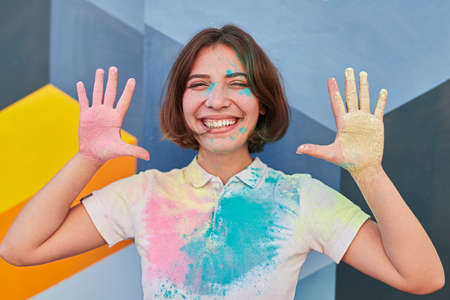 Laughing woman in messy paints of Holi festival