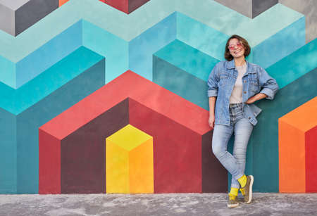 Cheerful young woman leaning on colorful wall