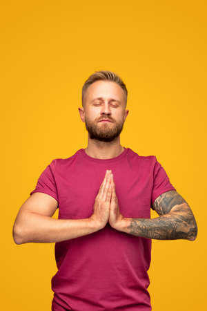 Calm modern guy meditating for stress relief