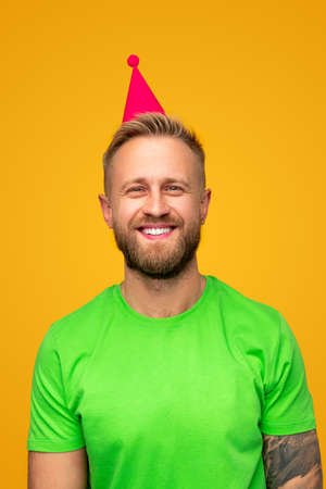 Laughing guy in party hat ready for celebration
