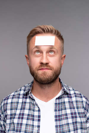 Puzzled man looking at empty sticker on forehead