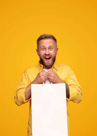 Excited bright man with blank paper bag