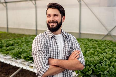 Happy male farmer near hydroponic table