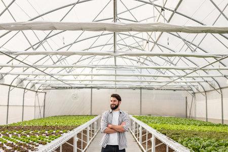 Confident farmer in hydroponic greenhouse Banco de Imagens