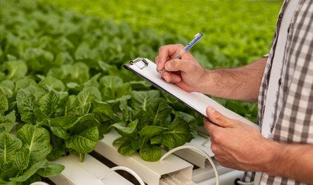 Crop farmer making notes near plants