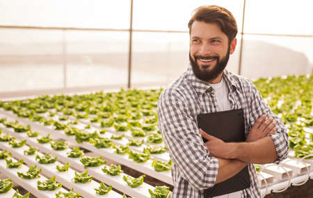 Happy gardener leaning on hydroponic table