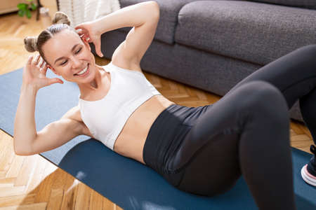 Cheerful sportswoman exercising on floor