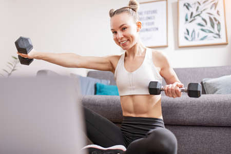 Slim woman exercising with dumbbells during online workout Banco de Imagens