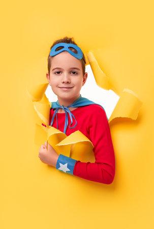 Little superhero peeking from hole in yellow paper Banco de Imagens