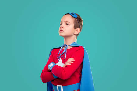 Serious little superhero looking away