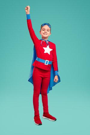 Happy little superhero clenching fist