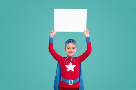 Happy little superhero with blank banner