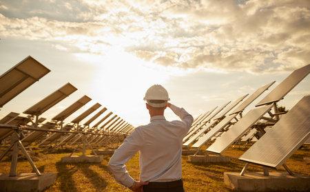 Unrecognizable engineer admiring modern solar farm at sunset Archivio Fotografico