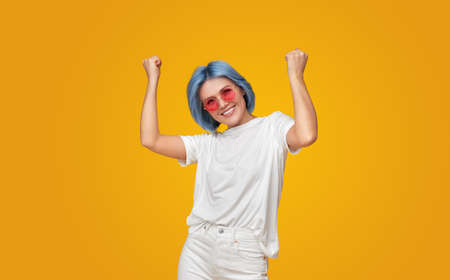 Cheerful woman with dyed hair celebrating success