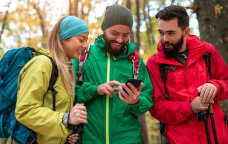 Happy hikers using smartphone in forest