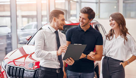 Male dealer selling car to couple