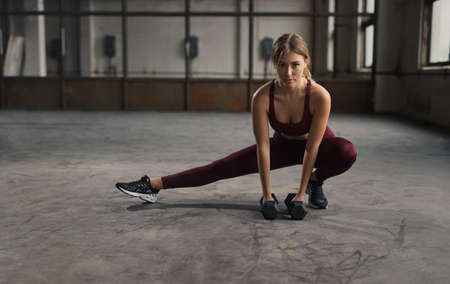 Female athlete lunging with dumbbells