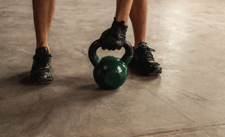 Crop sportsman lifting kettlebell from floor
