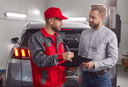 Customer and mechanic with checklist discussing work in auto service center