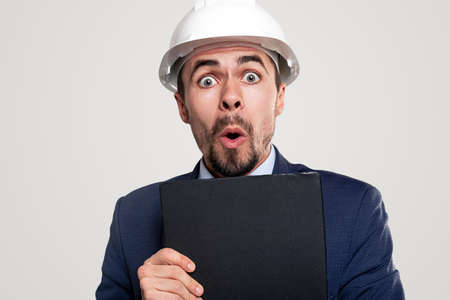 Shocked contractor with clipboard looking at camera Banque d'images