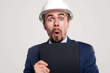 Shocked contractor with clipboard looking at camera Foto de archivo