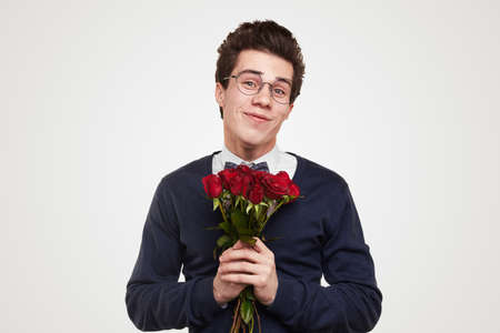 Romantic young man with bouquet of roses