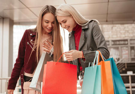 Happy stylish women discussing purchases after shopping