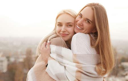 Cheerful women hugging and looking at camera