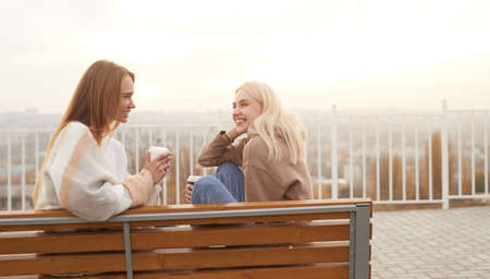 Cheerful girlfriends with takeaway coffee chatting on bench Imagens
