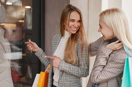 Cheerful girlfriends standing near shop window
