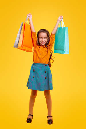 Excited little girl with shopping bags in raised hands