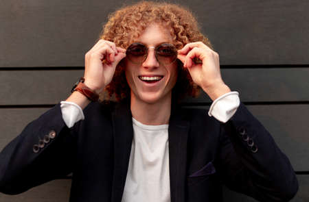 Cheerful stylish man in trendy sunglasses