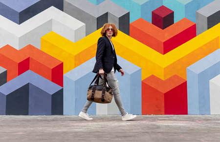 Stylish young guy walking on street near colorful graffiti wall