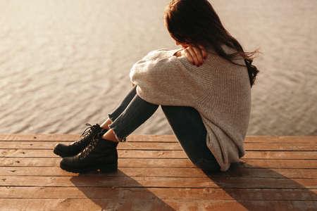 Sad woman sitting on pier near water
