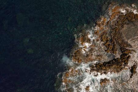 Rocky coast of wavy sea with foamy waves 免版税图像