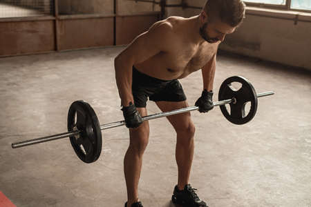 Strong man exercising with barbell in gym