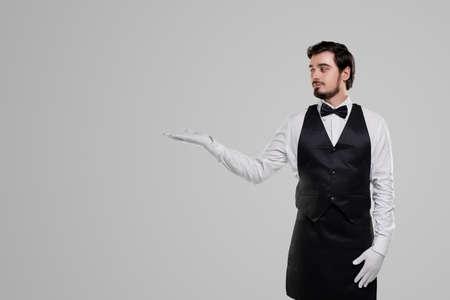 Elegant waiter pointing aside on blank space