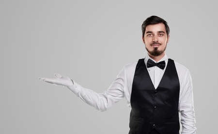 Confident waiter showing blank space