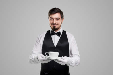 Elegant waiter with cup of coffee 免版税图像