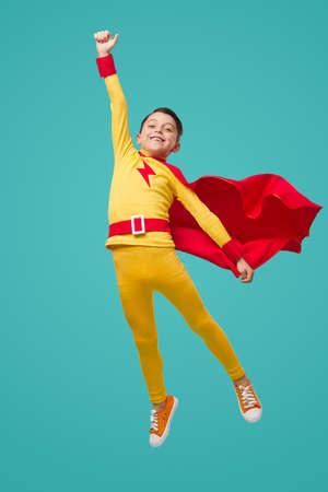 Energetic superhero kid flying with arm raised 免版税图像