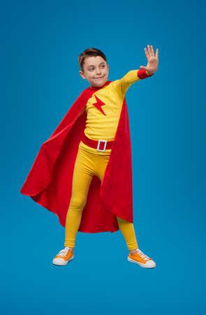 Cheerful kid in superhero costume showing stop gesture 免版税图像