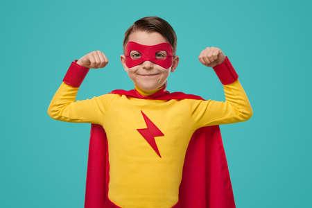 Proud superhero kid in mask showing biceps 免版税图像