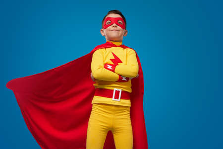 Confident superhero kid in costume and mask