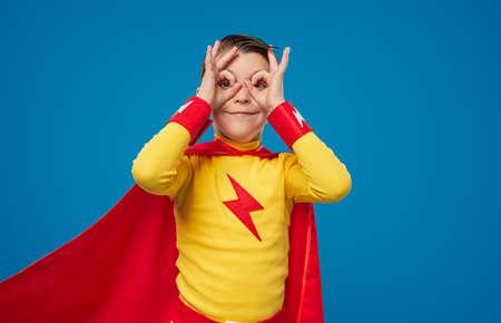Happy superhero kid looking through fingers