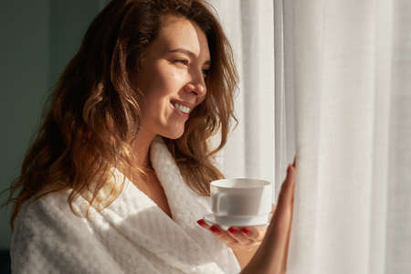 Happy woman with coffee looking at window 免版税图像